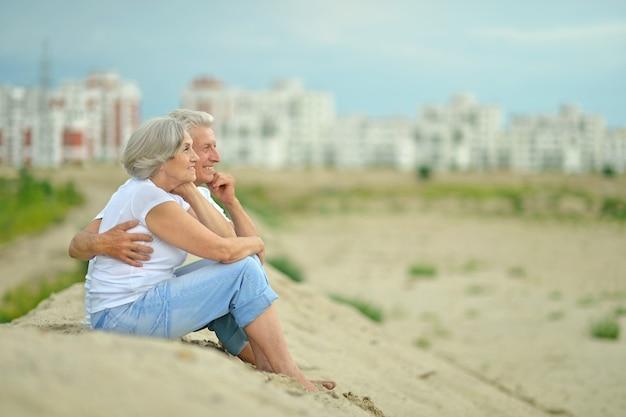 Zabawna starsza para odpoczywająca siedząc na piasku