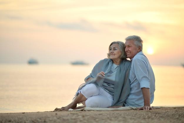 Zabawna starsza para poszła na plażę, aby cieszyć się morską bryzą