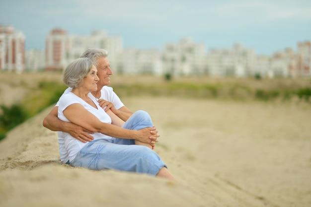 Zabawna starsza para siedząca na plaży w objęciach