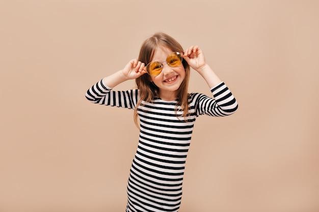 Zabawna szczęśliwa 6-letnia dziewczyna w sukience z paskiem na sobie okrągłe pomarańczowe okulary odwracając wzrok z czarującym uśmiechem na beżowym tle