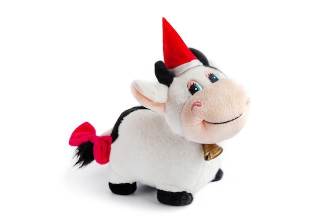 Zabawna toya miękka krowa z dzwoneczkiem na szyi, świątecznym kapeluszem i różową kokardką na ogonie