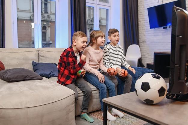 Zabawna trójka przyjaciół dzieci siedzi na kanapie w domu i cieszy się meczem piłki nożnej
