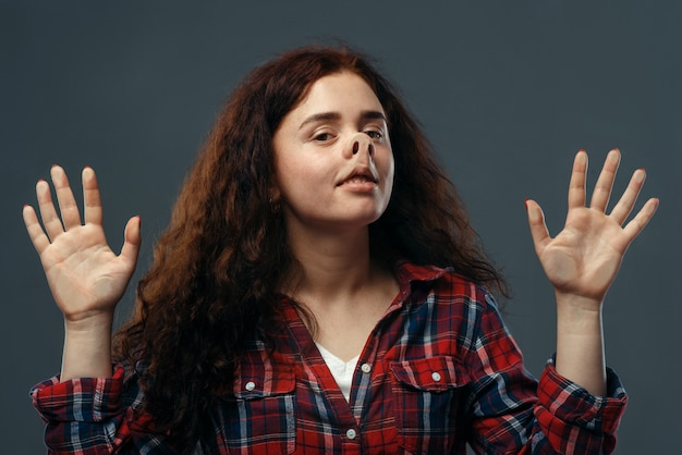 Zabawna twarz młodej kobiety zgnieciona na przezroczystym szkle.