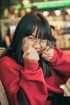 Zabawna twarz nastolatka azjatyckiego podnosi widelec i łyżkę w jadalni