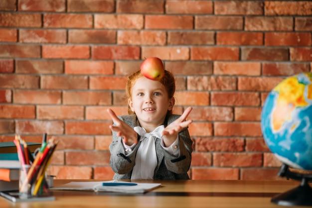 Zabawna uczennica bawi się jabłkiem przy stole w klasie.