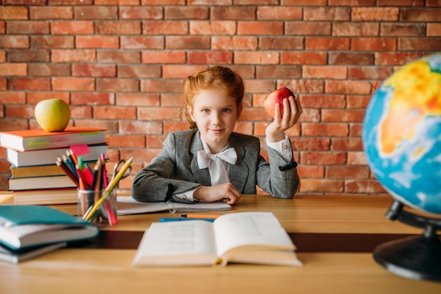 Zabawna uczennica z jabłkiem siedzi przy stole