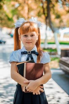 Zabawna urocza mała dziewczynka z książkami w dłoniach, pierwszego dnia szkoły lub przedszkola. dziecko jest na zewnątrz w ciepły słoneczny dzień, koncepcja wraca do szkoły.