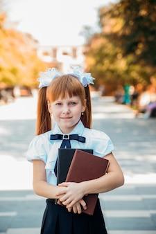 Zabawna urocza mała dziewczynka z książkami w dłoniach, pierwszego dnia szkoły lub przedszkola.