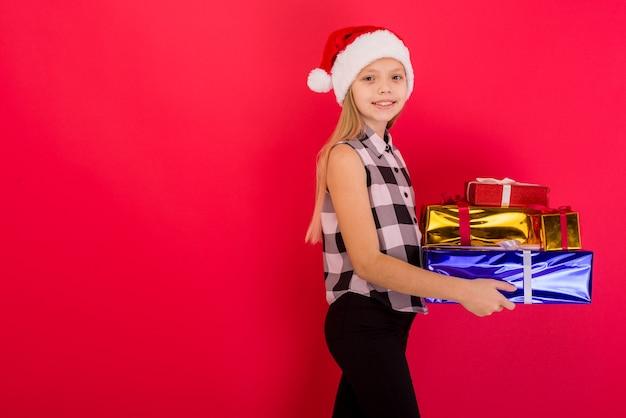 Zabawna uśmiechnięta radosna dziewczyna dziecko w kapeluszu santa gospodarstwa prezent świąteczny w ręku na czerwonym tle - obraz