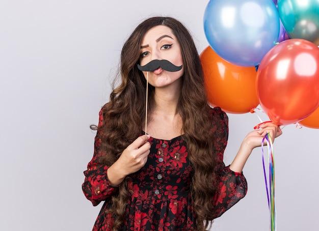 Zabawna wątpliwa młoda dziewczyna trzyma balony i fałszywe wąsy na patyku nad ustami, patrząc na kamery z zaciśniętymi ustami na białym tle na białej ścianie