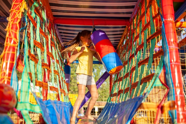 Zabawna wesoła dziewczynka bije kolorową torbę bokserską w dużym centrum rozrywki z miękkim kolorowym sprzętem