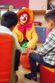 Zabawna zabawa klauna z wesołymi dziećmi razem.