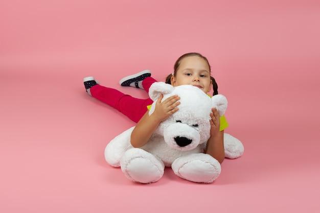 Zabawna, zadowolona dziewczyna leży na podłodze i przytula białego misia