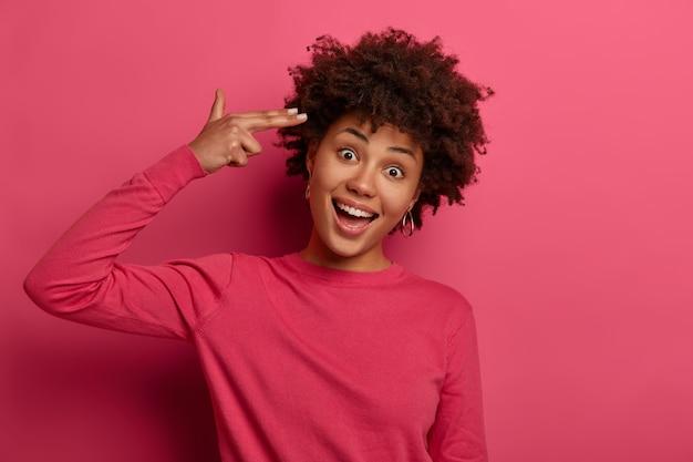 Zabawna zadowolona młoda kobieta wykonuje gest samobójczy, pistolet na palec, strzela w świątyni, przechyla głowę, nosi szkarłatny sweter, odizolowany na różowej przestrzeni