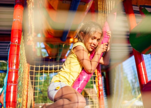 Zabawna, zalana łzami dziewczyna siedzi na dywanie i ociera łzy w centrum rozrywki z kolorowym sprzętem