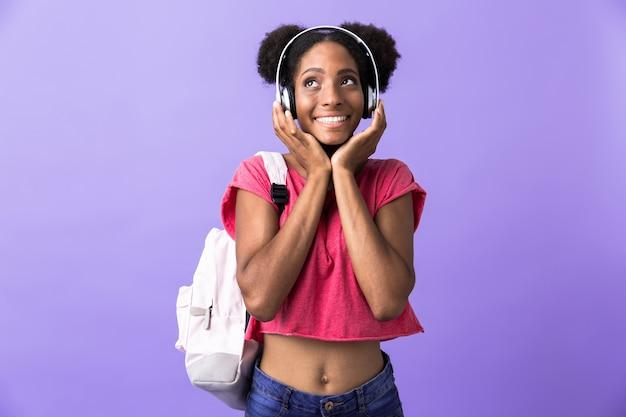 Zabawne african american kobieta na sobie plecak i białe słuchawki do słuchania muzyki, na białym tle