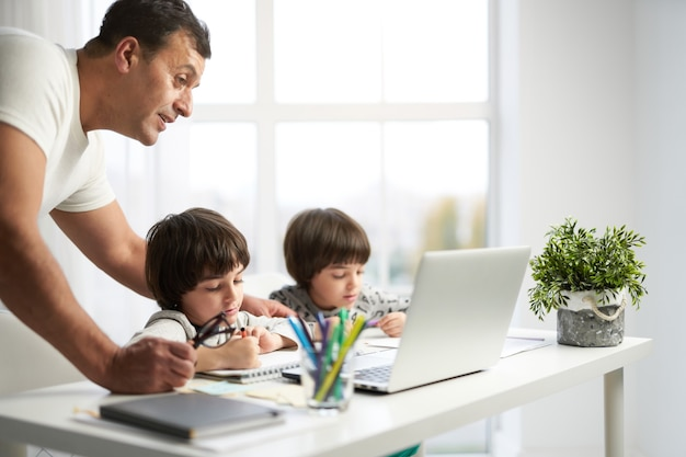Zabawne dzieci. latynoscy chłopcy rysują obrazki podczas lekcji online dla dzieci. ojciec spędza czas z dziećmi w domu