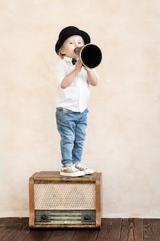 Zabawne dziecko bawiące się w domu. dziecko krzyczy przez megafon vintage. komunikacja i koncepcja kina retro