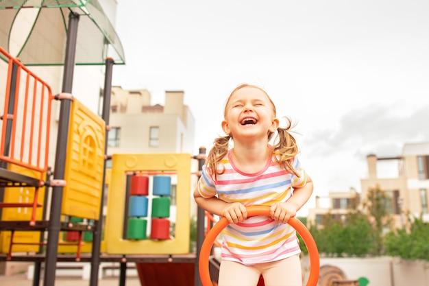 Zabawne dziecko dziewczynka gra na placu zabaw na świeżym powietrzu. śmiech wyrażenie dziecko bawi się na huśtawce z matką. szczęśliwa chwila i dobre emocje. aktywny wypoczynek sportowy dla dzieci. miejsce, miejsce na tekst