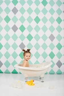 Zabawne dziecko dziewczynka kaukaski kąpieli i zabawy z zabawkami wody w pobliżu kwiatów