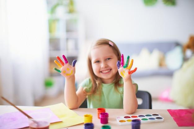 Zabawne dziecko pokazuje dłoniom pomalowaną farbę.