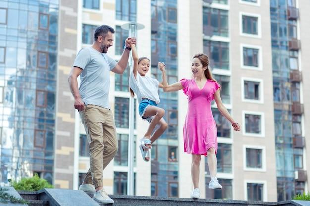 Zabawne dziecko. szczęśliwa miła dziewczyna skacze, trzymając się za ręce rodziców