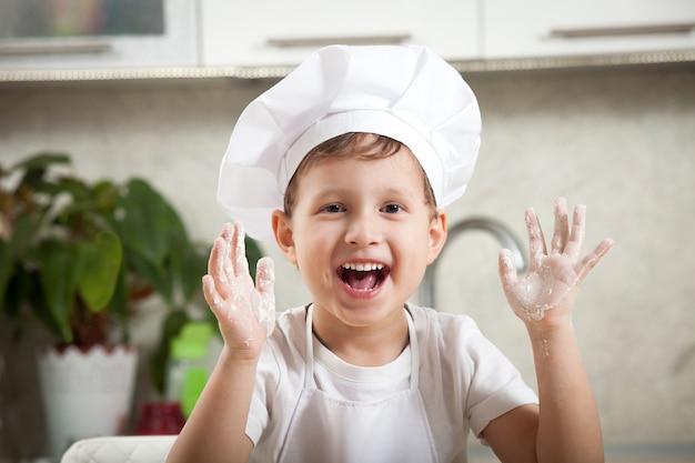 Zabawne dziecko z mąką, szczęśliwy emocjonalny chłopiec uśmiecha się radośnie