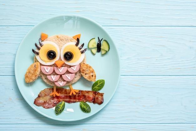 Zabawne jedzenie dla dzieci - słodkie tosty kanapkowe z małą sową z kiełbaskami i jajkami