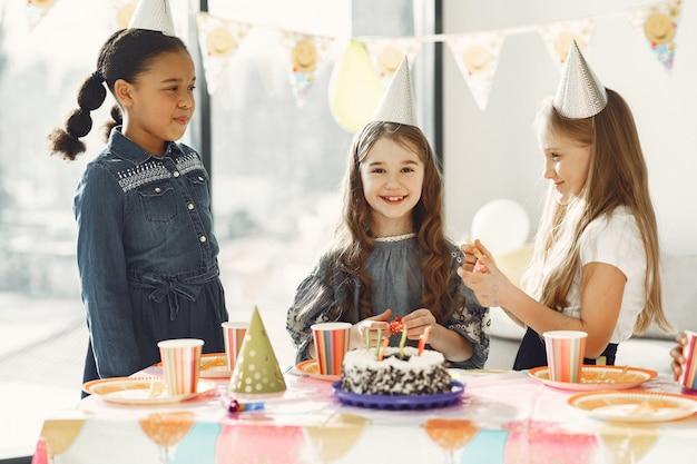 Zabawne przyjęcie urodzinowe dla dzieci w urządzonym pokoju. szczęśliwe dzieciaki z ciastem i balonami.