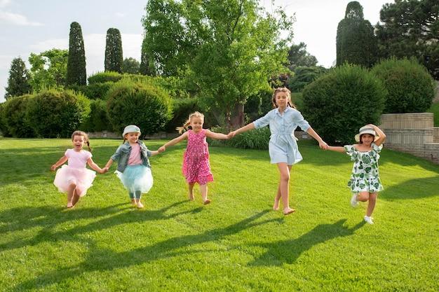 Zabawne się zaczyna. koncepcja mody dla dzieci. grupa nastoletnich chłopców i dziewcząt biegających w parku. kolorowe ubrania dla dzieci, styl życia, koncepcje modnych kolorów.