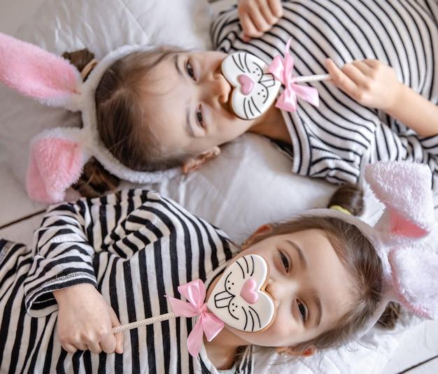 Zabawne siostrzyczki z wielkanocnymi pierniczkami w postaci buzi króliczków i uszami króliczka.