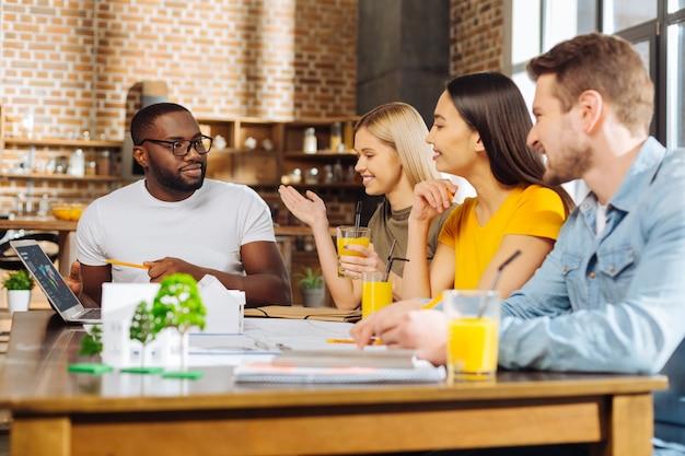 Zabawne studiowanie. czterech kreatywnych, energicznych uczniów siedzących przy stole, rozmawiając i planując strategię