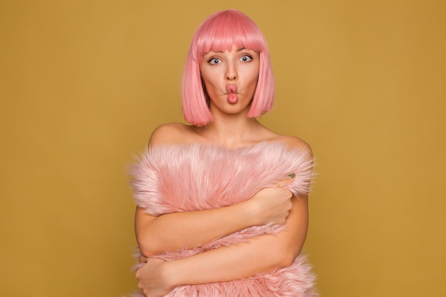 Zabawne ujęcie młodej atrakcyjnej różowowłosej kobiety z krótką modną fryzurą robiącą miny, pozując na ścianie musztardy z uroczą futrzaną poduszką w dłoniach