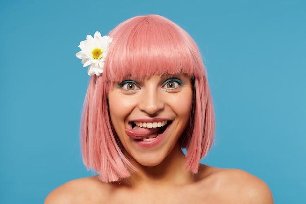 Zabawne ujęcie radosnej młodej atrakcyjnej kobiety z krótkimi różowymi włosami wystającymi jej język, patrząc wesoło w kamerę, na sobie kolorowy makijaż, pozując na niebieskim tle