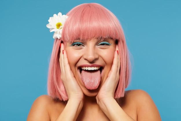 Zabawne ujęcie wesołej młodej uroczej różowowłosej kobiety z modną fryzurą, trzymając twarz z podniesionymi dłońmi, pozując na niebieskim tle, oszukując i pokazując język w aparacie