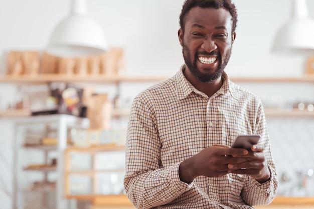 Zabawne wiadomości. rozradowany młody człowiek stojący w kawiarni i śmiejący się głośno, czytając śmieszne wiadomości tekstowe od znajomych na swoim telefonie