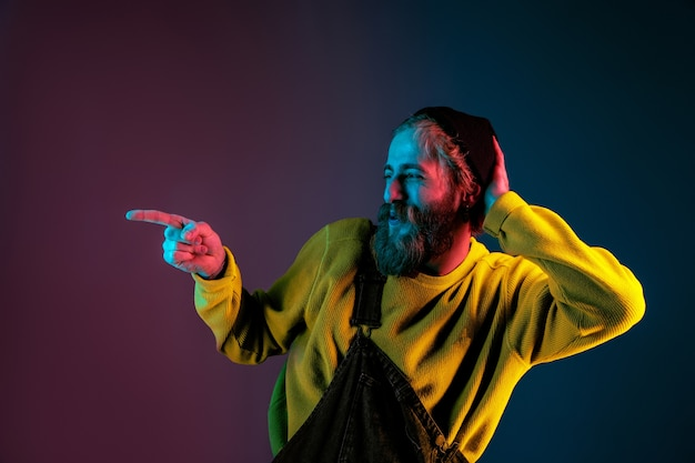 Zabawne, wskazując na bok. portret mężczyzny rasy kaukaskiej na przestrzeni gradientu w świetle neonu