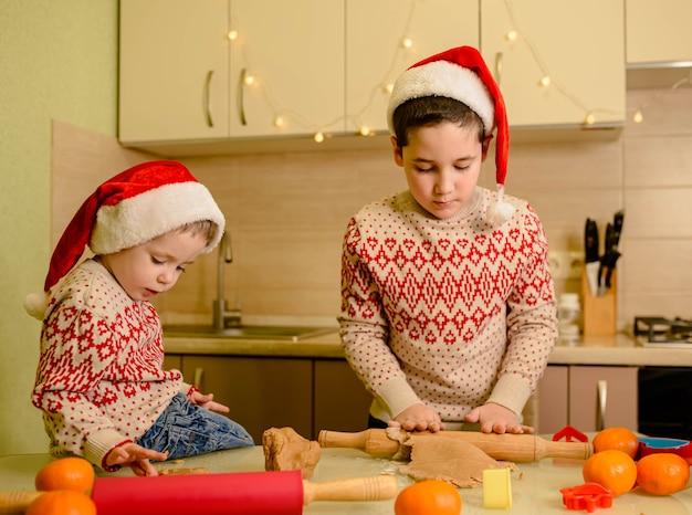 Zabawni mali chłopcy pieczą domowe świąteczne pierniki. domowe wypieki