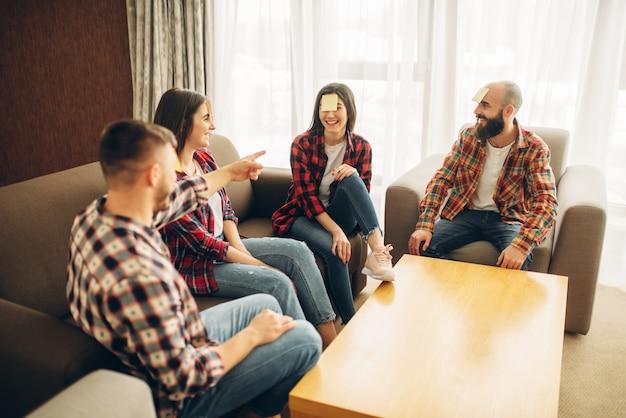 Zabawni przyjaciele grający notatki z naklejkami na czoło. firma bawiąca się kim jestem przy stole w domu, ludzie odgadują charakter