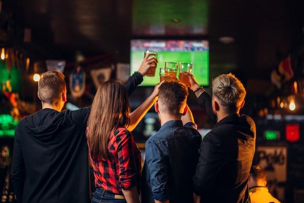 Zabawni przyjaciele oglądają piłkę nożną w telewizji i podnoszą szklanki z piwem w barze sportowym, szczęśliwi kibice, świętują zwycięstwo w grze