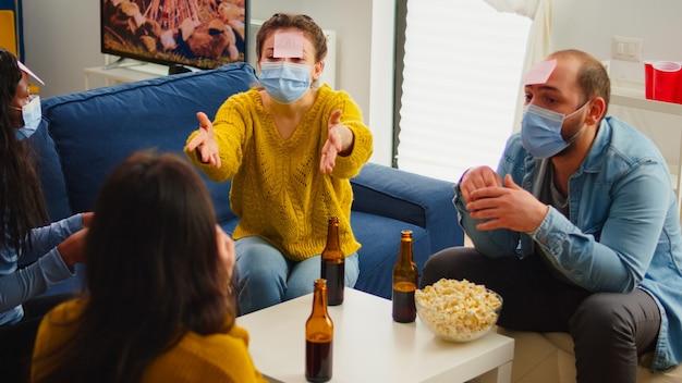 Zabawni przyjaciele z karteczkami samoprzylepnymi na czołach, cieszący się grą w imię gestykulując podczas nowej normalnej imprezy, nosząc maskę na twarz, zachowując dystans społeczny zapobiegając rozprzestrzenianiu się covid19. osoby cieszące się butelkami piwa?