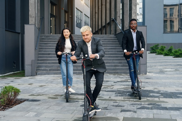 Zabawni, radośni, wielorasowi koledzy z biura mający wyścigi na skuterach elektrycznych w pobliżu nowoczesnych