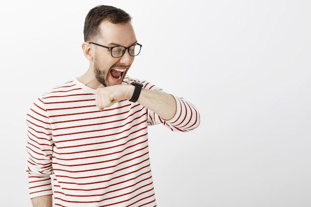 Zabawnie krzyczący europejczyk w okularach, podnoszący rękę przy twarzy i krzyczący na czarny zegarek cyfrowy, wydający polecenie osobistemu asystentowi lub rozmawiający z klientem za pośrednictwem urządzenia