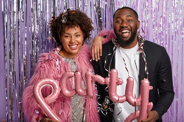 Zabawnie uśmiechnięta ciemnoskóra kobieta i mężczyzna cieszy się wolnym czasem na imprezę, trzymaj balon w kształcie litery
