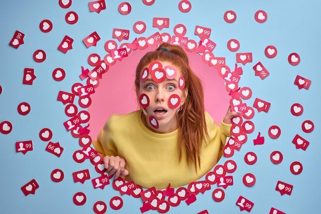 Zabawnie zaskoczona rudowłosa kobieta stoi w szoku, otrzymując wiele stawek za post, lubi podpisywać guziki w kształcie serca na twarzy