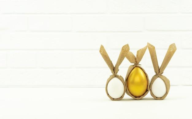 Zabawnie zdobione i pomalowane złote jajka stoją na białym stole w kuchni