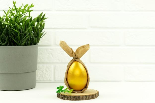 Zabawnie zdobione i pomalowane złote jajko leży na drewnianym talerzu na wielkanoc