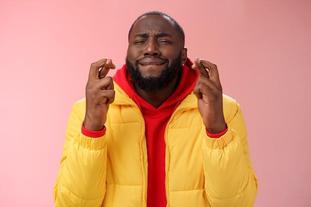 Zabawny afroamerykanin, brodaty mężczyzna w żółtym płaszczu, czerwona bluza z kapturem, ściągający usta, zamknięte oczy, skrzyżowane palce, powodzenia, zmartwienie, nadzieja, że marzenie się spełni, przewidywanie szczęścia stojąc wiernie na różowym tle