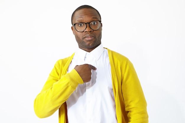 Zabawny afroamerykanin w stylowych okularach wyraża szok i pełne niedowierzanie do wyboru spośród innych, wskazując na siebie palcem wskazującym i pytając: masz na myśli mnie. wyraz twarzy człowieka
