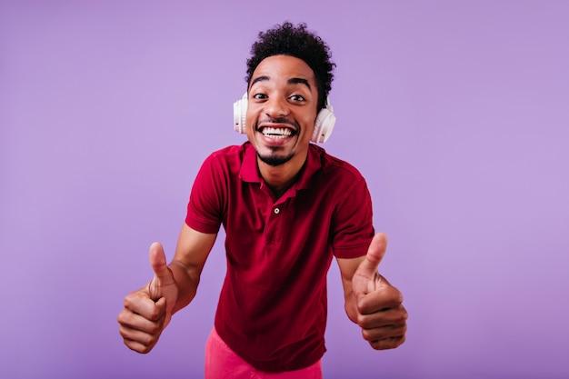 Zabawny afrykański model z falistymi włosami, wygłupiając się. kryty zdjęcie przystojnego studenta w dużych słuchawkach.